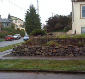 seattle older vintage home aging concrete retaining wall replacement new rockery street view